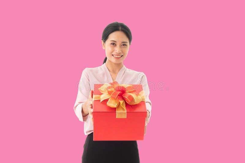 一个愉快的微笑的女孩藏品礼物盒的画象 图库摄影
