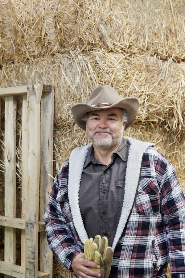 一个愉快的成熟人的画象有拿着在干草堆前面的牛仔帽的手套 免版税图库摄影