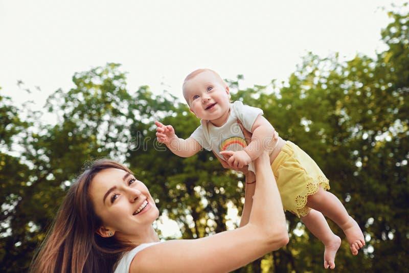 一个愉快的母亲使用与一个小孩在公园 图库摄影