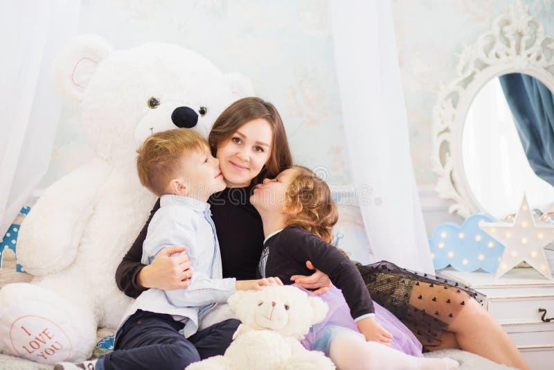 一个愉快的母亲和她的两个小孩的画象-男孩和女孩 幸福家庭画象 小孩亲吻母亲 图库摄影