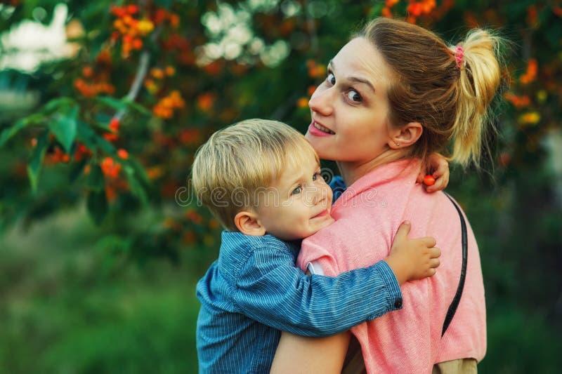 一个愉快的母亲的画象有她的儿子的夏天步行的 库存图片