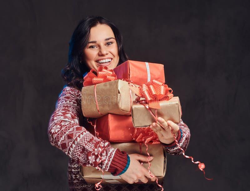 一个愉快的深色的女孩的画象穿一件温暖的毛线衣拿着礼物盒,隔绝在黑暗的织地不很细背景 图库摄影