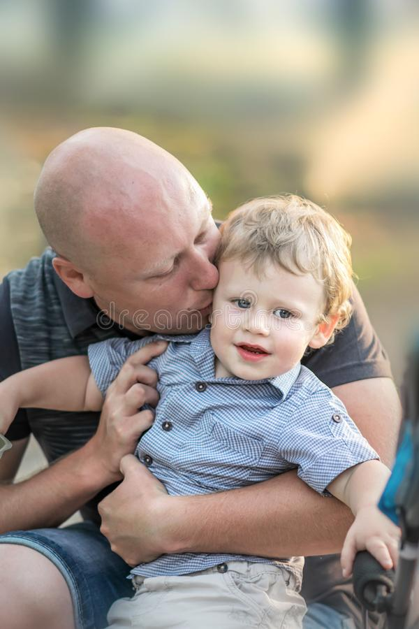 一个愉快的男婴和亲吻他夏天公园的年轻父亲 拥抱和亲吻他的小儿子的一个爱恋的父亲 父母亲爱, 免版税库存图片