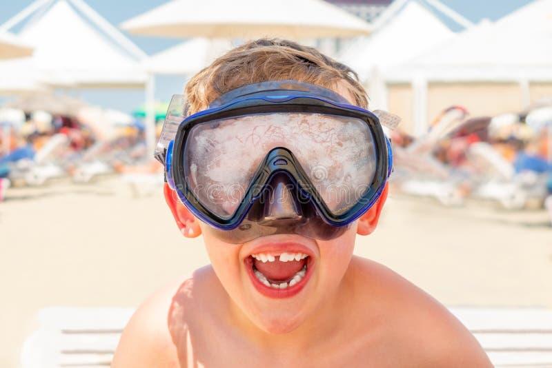 一个愉快的笑的男孩的特写镜头画象有潜水面具的在一个晴朗的海滩 免版税库存照片