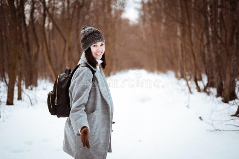 一个愉快的美丽的女孩的画象有棕色头发的在冬天森林在行家样式,生活方式穿戴了 免版税库存图片
