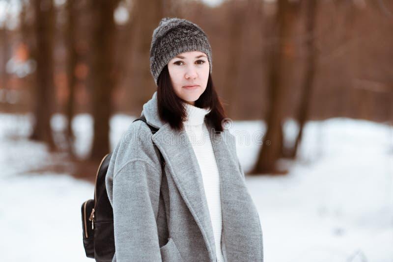 一个愉快的美丽的女孩的画象有棕色头发的在冬天森林在行家样式,生活方式穿戴了 库存图片