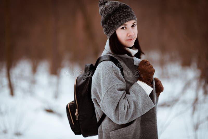 一个愉快的美丽的女孩的画象有棕色头发的在冬天森林在行家样式,生活方式穿戴了 免版税库存照片