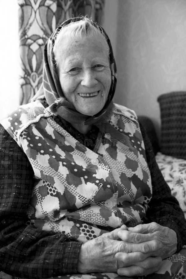 一个愉快,微笑的老妇人,祖母,前辈是烘烤,烹调在厨房里在舒适家 中间欧洲文化 免版税库存照片