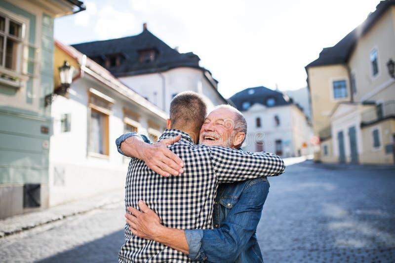 一个成人行家儿子和他的资深父亲在镇里,拥抱 库存照片