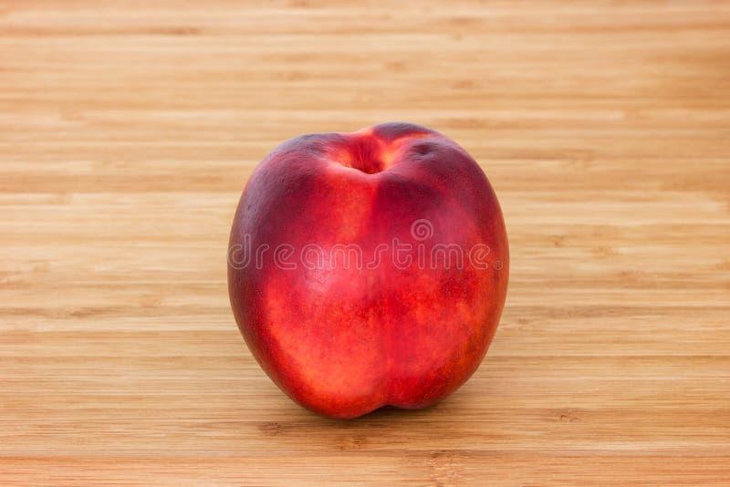 一个成熟油桃的特写镜头在一块砧板的 免版税库存图片