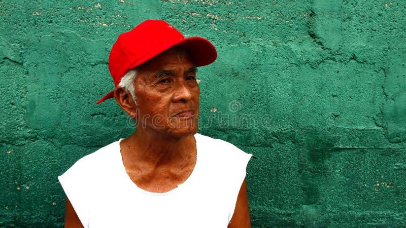 一个成熟的菲律宾人站立对绿色墙壁 库存图片