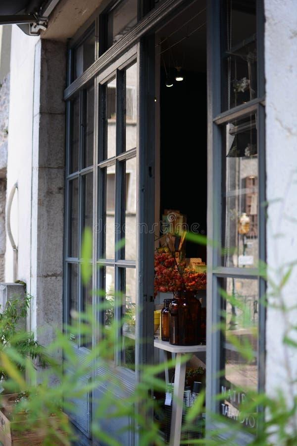 一个房子的一个半被打开的窗口的垂直的射击有庭院的在前面 免版税库存图片