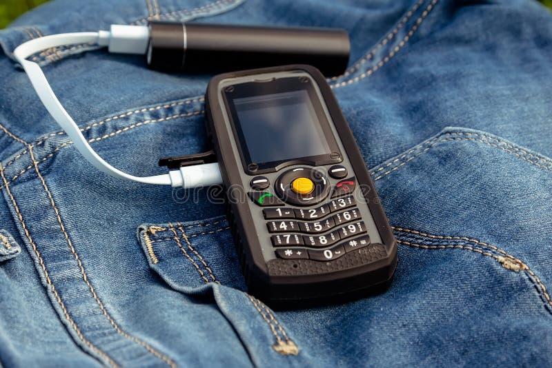 一个手机和力量在牛仔裤背景开户本质上 库存图片