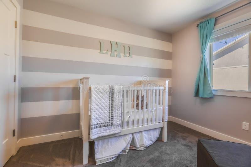 一个托儿所的内部有白色小儿床和组合图案信件的在镶边墙壁上 免版税图库摄影