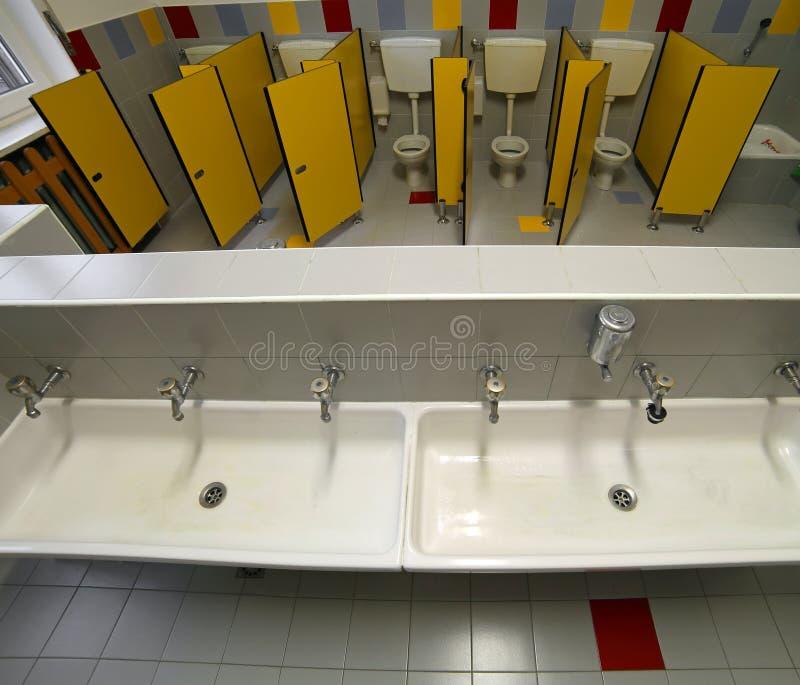 一个托儿所的卫生间有小洗手间和陶瓷水槽的 图库摄影