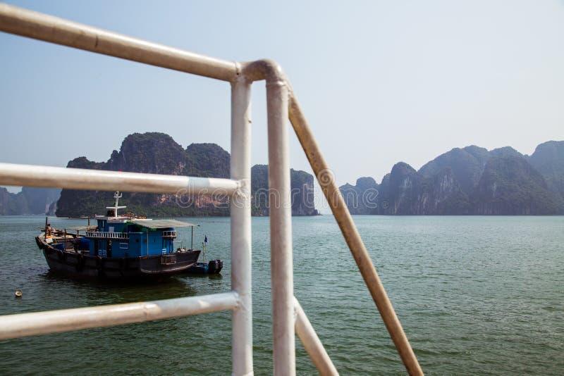 一个拖轮航行通过海岛在下龙湾 免版税库存照片