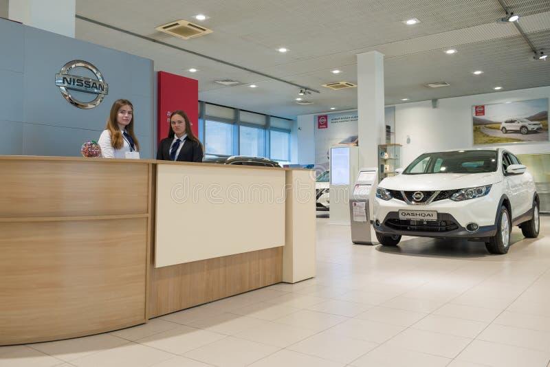 一个招待会的两个女孩日产公司的正式经销商的汽车展示会的 图库摄影