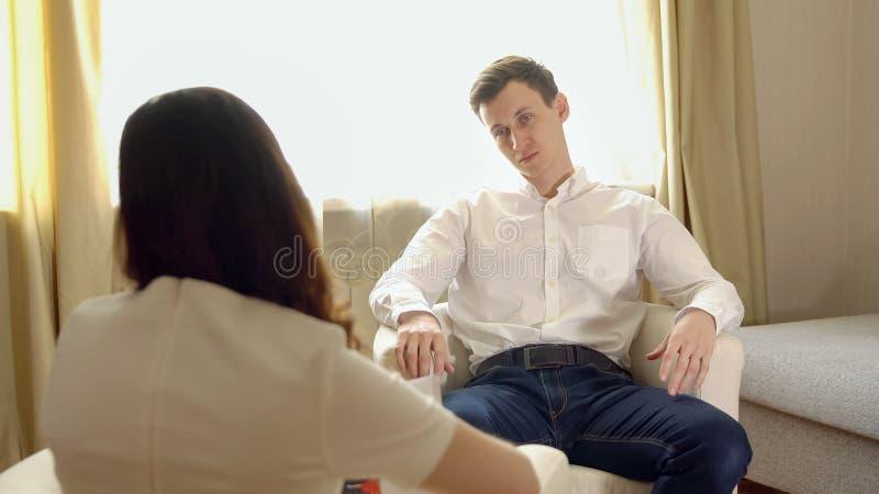 一个招待会的年轻人有一位女性心理学家的 免版税库存照片