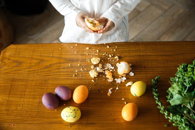 一个捣毁的鸡蛋在一些被绘的鸡蛋旁边的一张桌放置 少女在背景站立 免版税库存照片