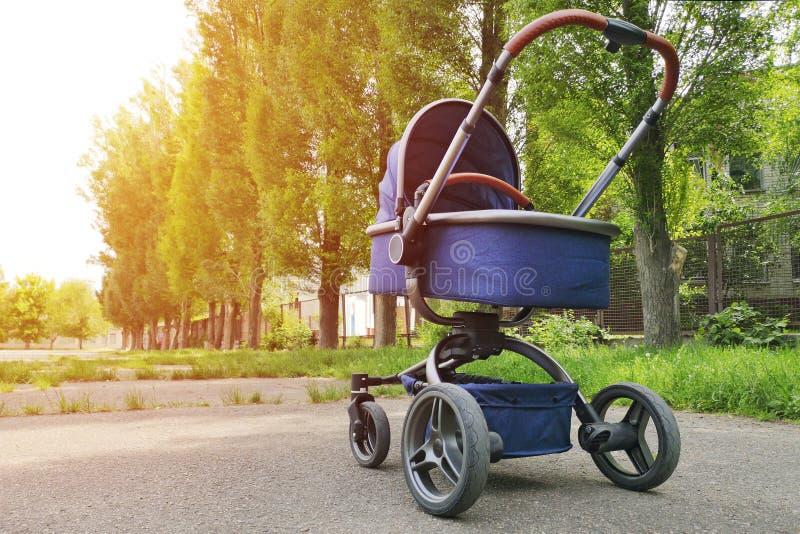 一个摇篮车婴孩在公园在一好日子 走与支架的父母在城市公园 免版税库存照片