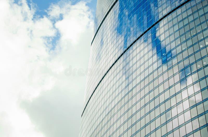一个摩天大楼的墙壁的片段有镜子玻璃的反对与云彩的天空 免版税图库摄影