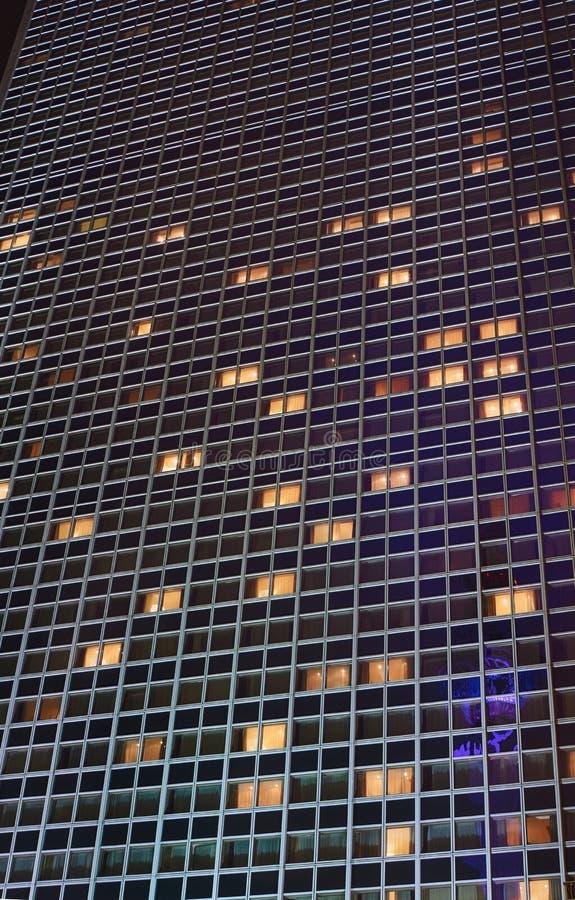 一个摩天大楼的门面在晚上 免版税库存照片