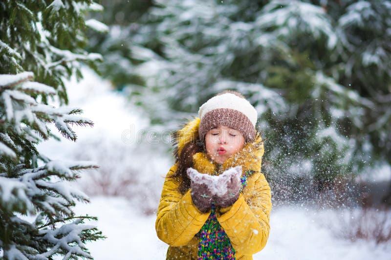 一个救生服的一个小女孩使用与雪在冬天 孩子在他的手上拿着雪 免版税库存图片