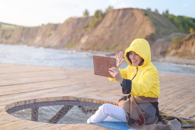 一个救生服的一名妇女为视频通信使用一种片剂在社会网络,坐一个木码头由海在黎明, 库存照片