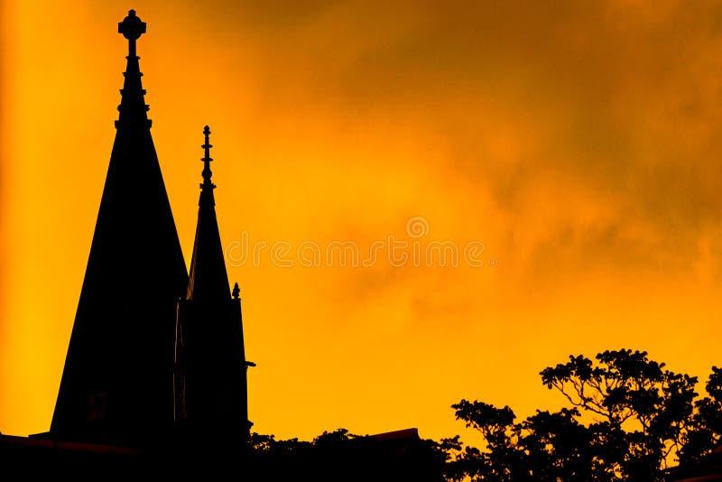 一个教会尖顶和高树分支的剪影,反对明亮的黄色火热天空在日落期间,哈林 库存图片