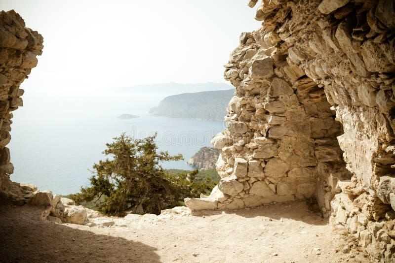 一个教会的废墟Monolithos城堡和美好的风景视图的,罗得岛海岛,希腊 看法通过遗骸  免版税库存照片