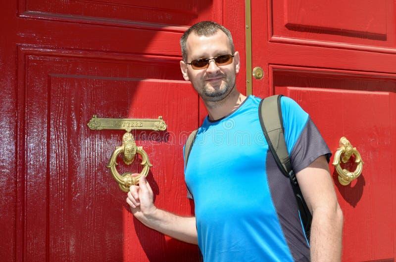 一个敲红门的男人 免版税库存照片
