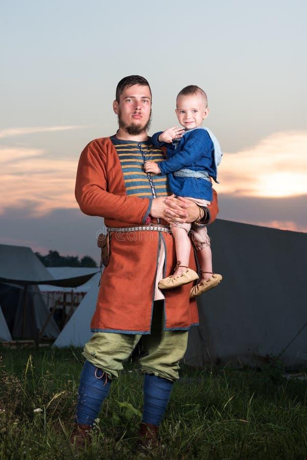 一个斯拉夫的人的垂直的画象有一个婴孩的历史服装的 免版税图库摄影