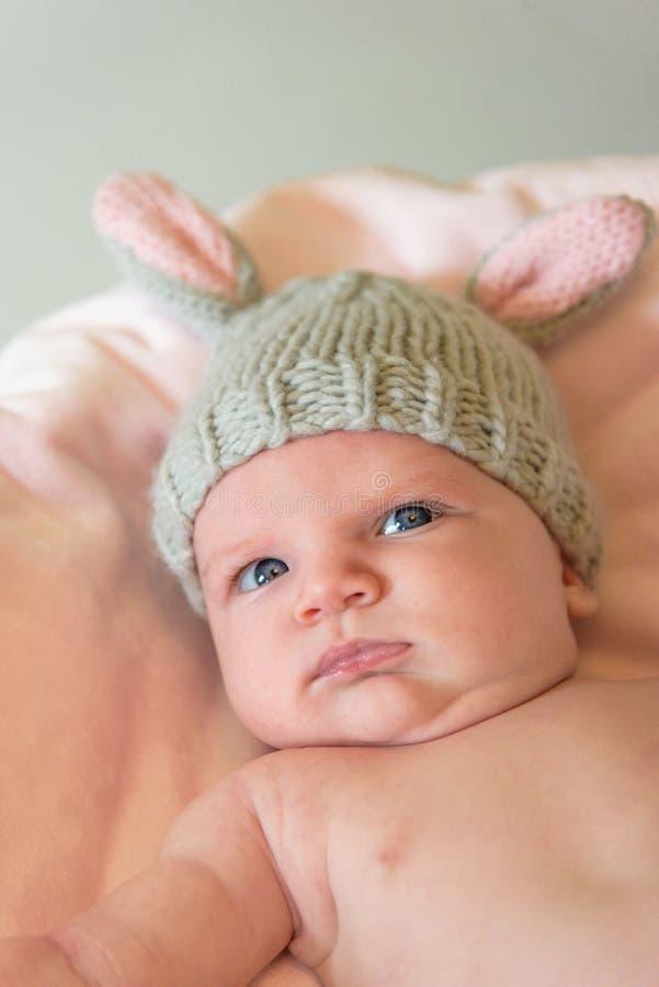 一个新出生的婴孩的特写镜头编织兔宝宝耳朵帽子的 免版税库存照片