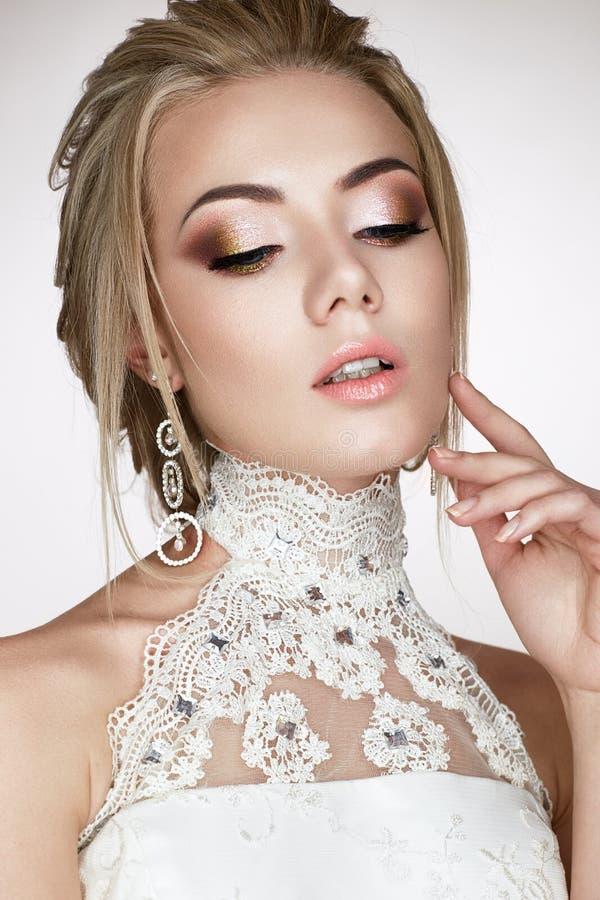 一个新娘的图象的一个女孩婚礼礼服和美丽的发光的耳环的 与明亮的构成和p的一个美好的模型 免版税库存图片