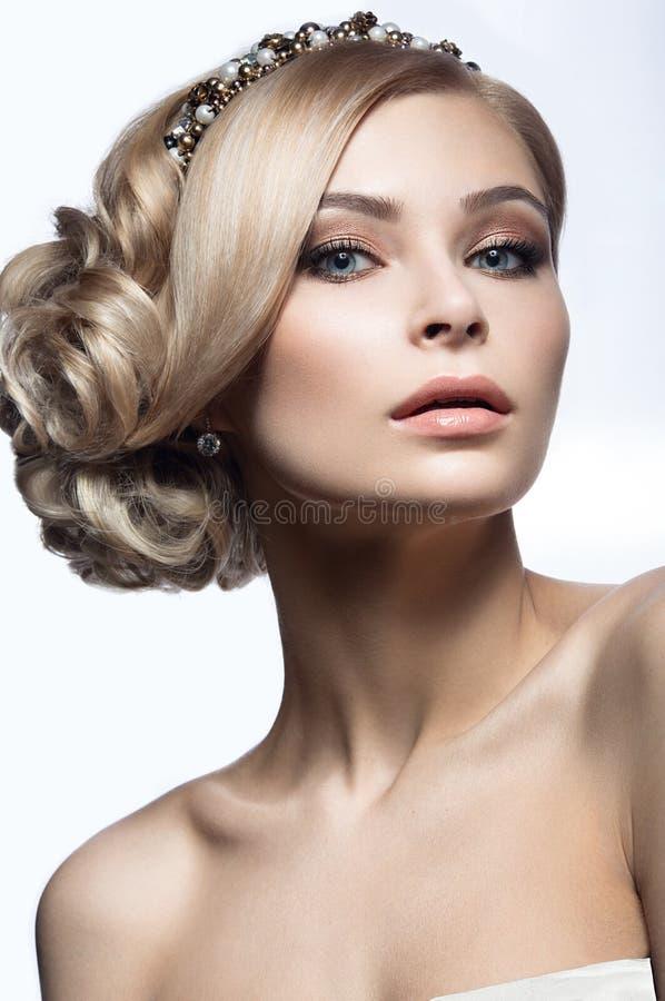 一个新娘的图象的美丽的白肤金发的女孩有一个冠状头饰的在她的头发 秀丽表面 背景镜象婚礼白色 库存图片