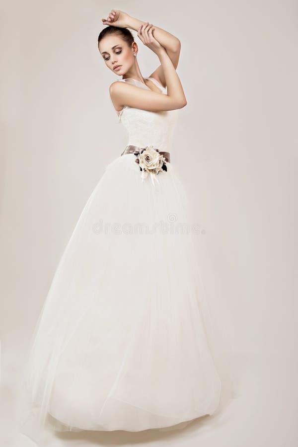以一个新娘的形式美好的女孩模型她的婚礼礼服的 秀丽表面 图库摄影