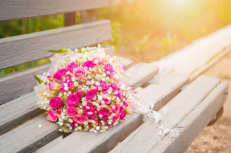 一个新娘的花束从桃红色玫瑰的在一个长木凳说谎根据落日 免版税库存照片
