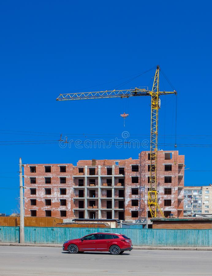一个新的公寓高大厦的建造场所与塔吊的反对蓝天 在一新的buil的背景的红色新的汽车 库存图片
