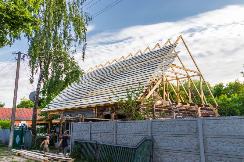 一个新的木屋顶的设施在一个寓所的由木匠和盖屋顶的人队  免版税库存照片
