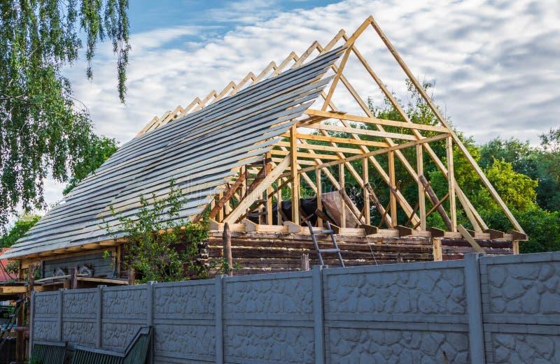 一个新的木屋顶的设施在一个寓所的由木匠和盖屋顶的人队  库存照片
