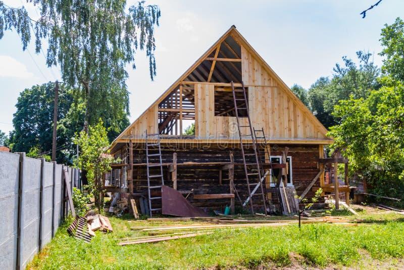 一个新的木屋顶的设施在一个寓所的由木匠和盖屋顶的人队  免版税库存图片