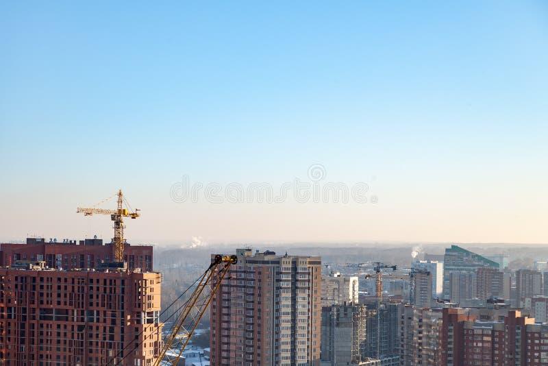 一个新的现代房子的鸟瞰图建设中有一架黄色塔吊的,红色灯笼在起重机结束时,大厦 免版税库存照片