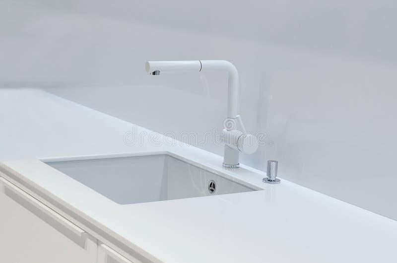 一个新的白色厨房水槽被做人为石头和龙头 现代厨房内部的概念 图库摄影