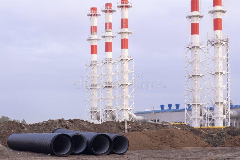 一个新锅炉房的红色管道,在蓝天下,有许多白色的 新建城市锅炉房 免版税库存照片