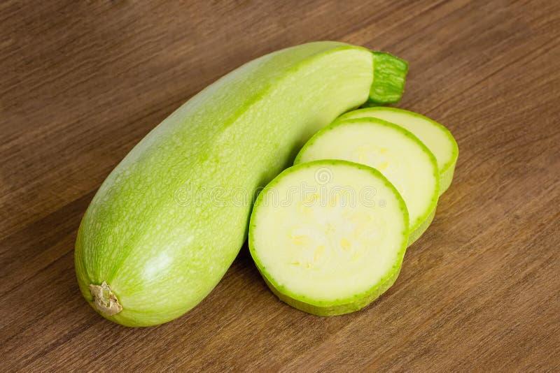 一个新鲜的绿色夏南瓜和少量切片在一个棕色木切板 : 新鲜农厂菜和健康 免版税库存照片