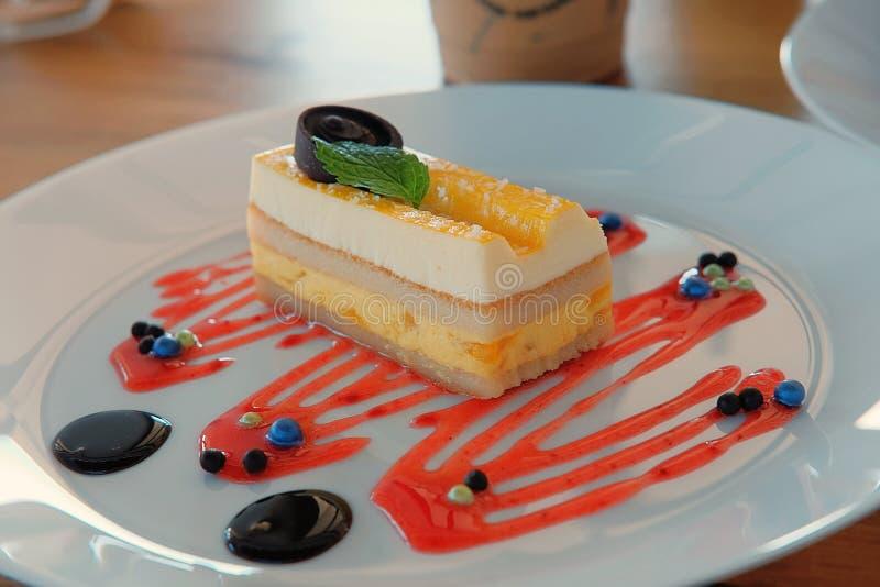 一个方形的片断乳酪蛋糕,那充满芒果奶油,安置在白色板材和装饰用巧克力 免版税库存图片