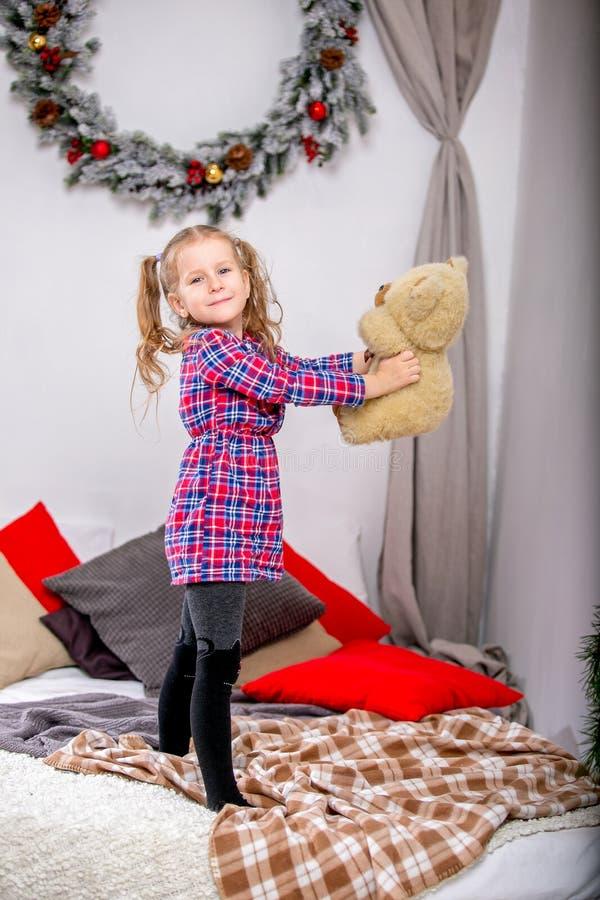 一个方格的青红色礼服身分的愉快的逗人喜爱的少女在与玩具熊和拿着它的床上衬托 免版税库存照片