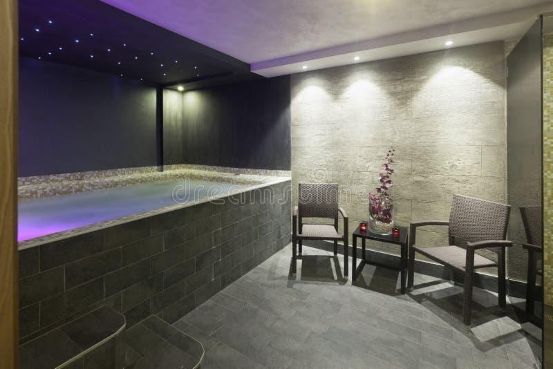一个旅馆温泉的内部与极可意浴缸浴的与四周光 免版税库存照片