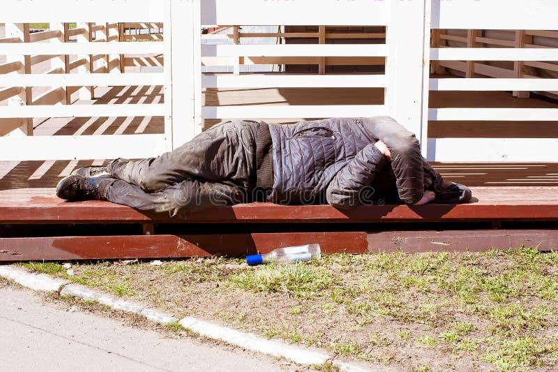 一个无家可归的人在街道上说谎,一个空的伏特加酒瓶在他旁边说谎 酒精问题 免版税库存照片