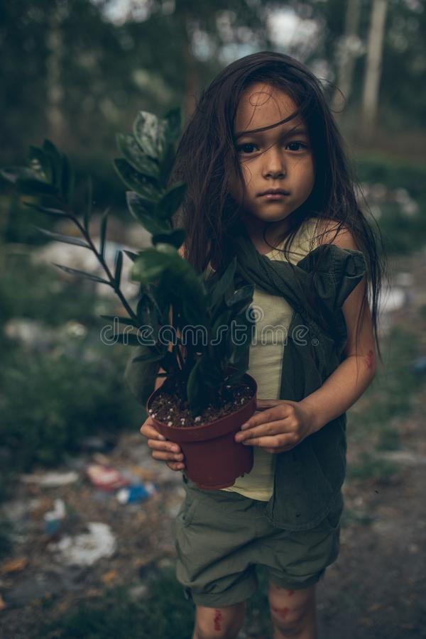 一个无家可归的女孩在与室内植物的一个垃圾堆站立在罐 免版税库存图片